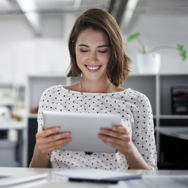 Businesswoman using her tablet at her desk