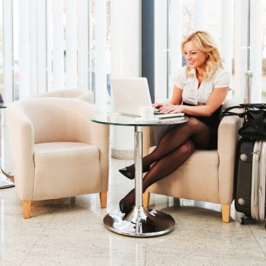 Business woman sitting in a hotel lobby with her suitcase and using her laptop.   [url=http://www.istockphoto.com/search/lightbox/9786622][img]http://dl.dropbox.com/u/40117171/business.jpg[/img][/url]