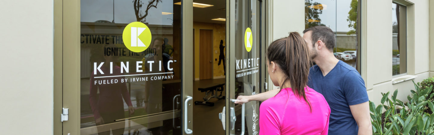 A man and woman walking into the KINETIC fitness center located ar Irvine Business Center in Irvine, CA