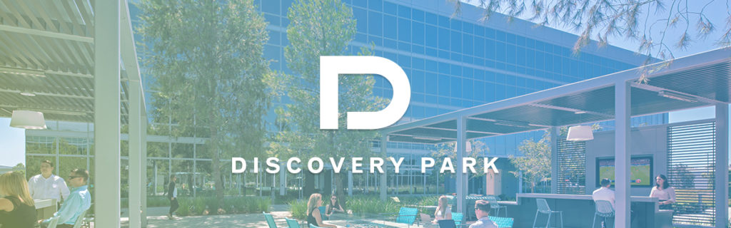 Photography of people enjoying The Commons, an outdoor workplace and gathering area, at The Quad at Discovery Park in Irvine, CA with the Discovery Park logo and filter overlaid