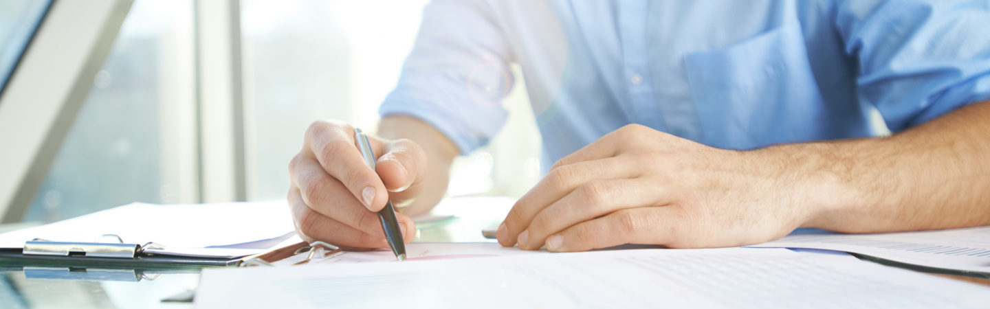 Man in a blue shirt holding a pen doing paperwork over a reflective table